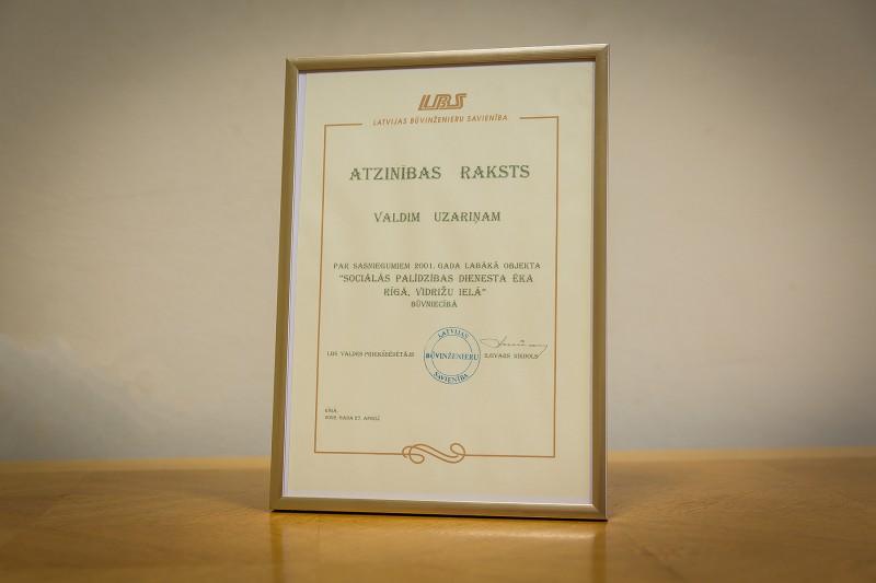 Latvijas Būvinženieru savienības atzinības raksts Valdim Uzariņam par sasniegumiem 2001. gada labākā objekta Sociālās palīdzības dienesta ēkas būvniecībā. Rīgā, 2002. gada 27. aprīlī.