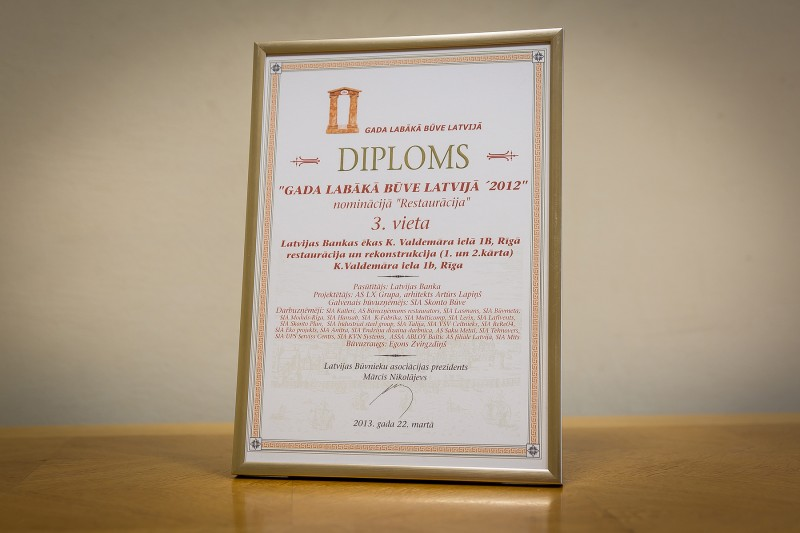 """Konkursa """"Gada labākā būve Latvijā 2012"""" atzinību nominācijā """"Restaurācija"""" (3. vieta) AS """"Būvuzņēmums Restaurators"""" saņēma 2013. gada 22. martā. Šis apbalvojums tika piešķirts par 2012. gadā veikto Latvijas Bankas klientu kases telpu restaurāciju un rekonstrukciju (1. un 2. kārta), kas atrodas Rīgā, Krišjāņa Valdemāra ielā 1b."""