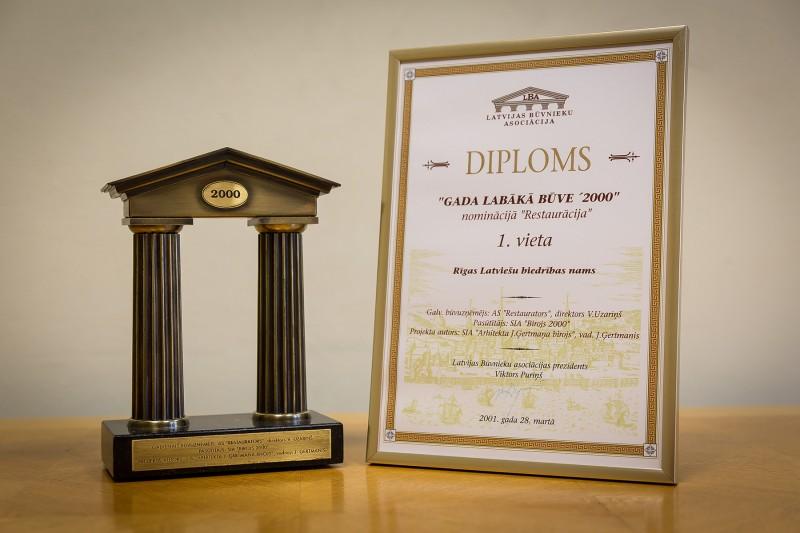 """Konkursa """"Gada labākā būve Latvijā 2000"""" atzinību nominācijā """"Restaurācija"""" (1. vieta) AS """"Restaurators"""" saņēma 2001. gada 28. martā. Šis apbalvojums tika piešķirts par 2000. gadā veiktajiem restaurācijas darbiem Rīgas Latviešu biedrības namā, kas atrodas Rīgā, Merķeļa ielā 13."""